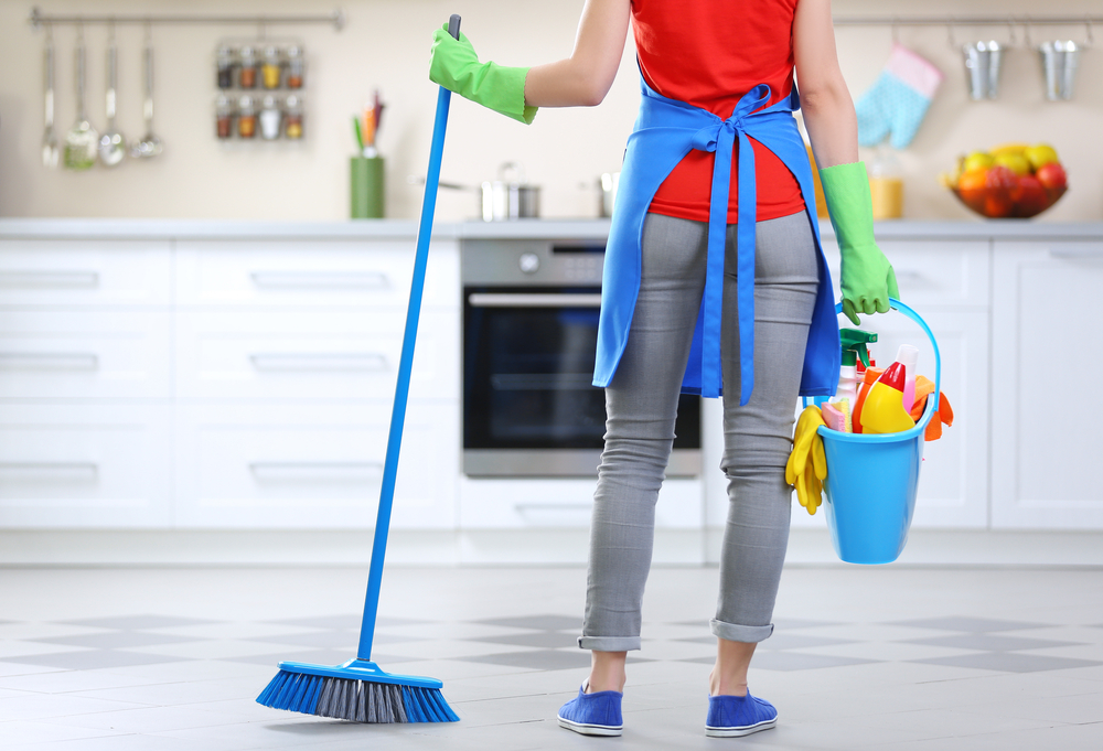 A woman facing away from the camera and holding cleaning supplies and a broom, getting ready to work.